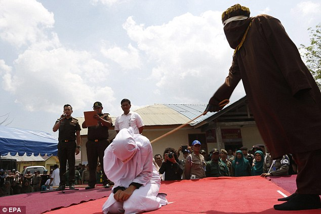Encolhida de medo em seus joelhos, uma mulher indonésia é chicoteada na frente de uma multidão … porque tinha começado a namorar